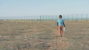 Un refugiado corriente feliz del niño pequeño entre desierto cerca de la frontera en día soleado almacen de metraje de vídeo