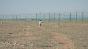 Un refugiado corriente feliz del niño pequeño entre desierto cerca de la frontera en día soleado metrajes