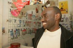 Un refugiado sudanés en sus accesorios del teléfono móvil hace compras Foto de archivo libre de regalías