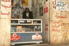 Un refugiado sudanés en sus accesorios del teléfono móvil hace compras Imágenes de archivo libres de regalías