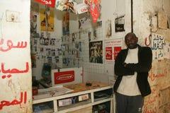 Un refugiado sudanés en sus accesorios del teléfono móvil hace compras Fotos de archivo