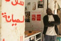 Un refugiado sudanés en sus accesorios del teléfono móvil hace compras Imagen de archivo libre de regalías