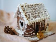 Un regalo al lado de una casa de pan de jengibre, paisaje de la Navidad imágenes de archivo libres de regalías