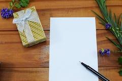 Un regalo con las flores y un lugar para la enhorabuena Fotos de archivo libres de regalías