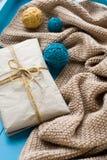 Un regalo da trovarsi accanto ai filamenti ed alla coperta luminosi della bobina Fotografie Stock