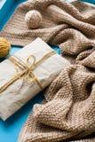 Un regalo da trovarsi accanto ai filamenti ed alla coperta luminosi della bobina Fotografia Stock Libera da Diritti