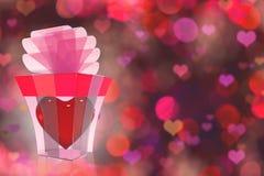 Un regalo dall'interno del cuore abbellito con il nastro e l'arco Immagini Stock