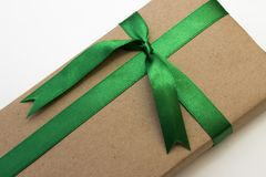 Un regalo de vacaciones envuelto en papel y atado con la cinta verde imagen de archivo
