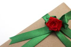 Un regalo de vacaciones envuelto en papel y atado con una cinta verde con una flor roja de la rosa imagen de archivo