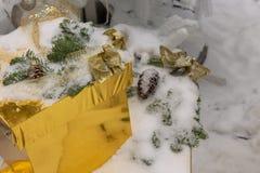 Un regalo en una caja del oro miente nieve-pulverizado fotografía de archivo libre de regalías