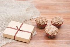 Un regalo en una caja y tres magdalenas foto de archivo