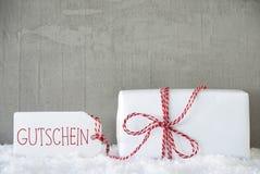Un regalo, il fondo urbano del cemento, il testo Gutschein significa il buono Immagini Stock