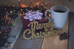Un regalo, una inscripción del oro y una taza de café en el tablen Imágenes de archivo libres de regalías