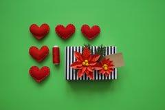 Un regalo in una scatola ed in biglietti di S. Valentino su un fondo verde I colori sono verdi, rossi, neri, Kraft e bianco Immagini Stock Libere da Diritti