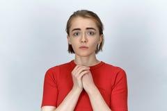 Un regard de plaidoirie triste d'une jeune femme attirante sur le petit morceau images stock