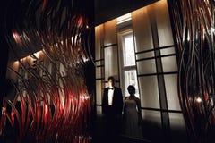 Un regard par les lampes rouges élégantes sur un couple de mariage Photos libres de droits