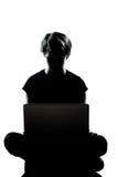 Un regazo computacional del ordenador de la silueta del adolescente Foto de archivo