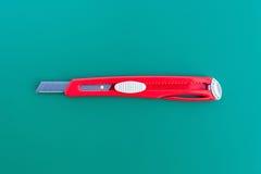 Un regla y un cortador en la estera verde del corte Imagenes de archivo