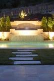 Un regroupement avec une cascade à écriture ligne par ligne dans une arrière-cour de luxe Images libres de droits