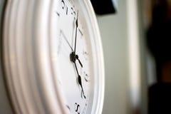 Un reloj blanco en la pared, nunca para el hacer tictac Imagen de archivo