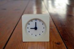 Un reloj blanco que indica la novena hora Foto de archivo libre de regalías