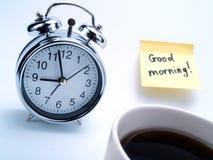 Un reloj de alarma, una taza de café y una nota amarilla Imagen de archivo libre de regalías