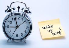 Un reloj de alarma y una nota amarilla Foto de archivo
