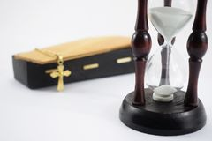 Un reloj de arena y un ataúd en un fondo blanco Fotos de archivo libres de regalías