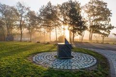 Un reloj de sol con salida del sol y siluetas de árboles Imagen de archivo libre de regalías