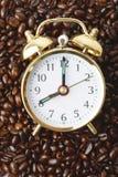 Un reloj en una cama de los granos de café Fotos de archivo libres de regalías