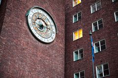Un reloj grande cerca de ventanas imagen de archivo