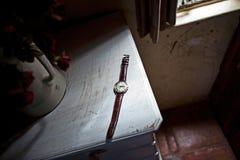 Un reloj se sienta en una tabla de cocina al lado de un travesaño de la ventana fotos de archivo libres de regalías
