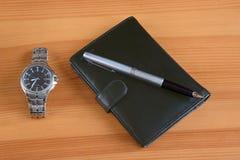 Un reloj, una pluma y una tarjeta de visita Imagen de archivo