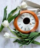 Un reloj, una taza de café y tulipanes Imagen de archivo libre de regalías