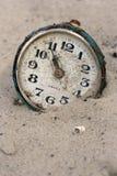 Un reloj viejo en la arena Imágenes de archivo libres de regalías