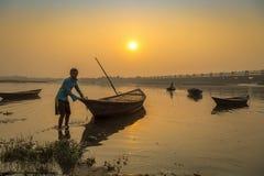Un remero intenta remolcar su barco para apuntalar en la puesta del sol en el río Damodar Fotos de archivo libres de regalías