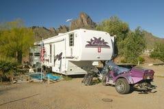 Un remolque, un vehículo campo a través y campistas en Arizona Foto de archivo libre de regalías
