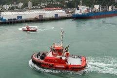 Un remorqueur et un bateau pilote manoeuvrant dans un port image libre de droits