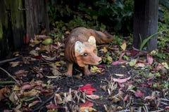 Un renard de plâtre parmi le feuillage dans le coin Photographie stock libre de droits