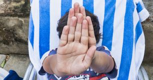 Un renversement de l'adolescence de garçon, couvre son visage de ses mains plan rapproch? de visage et de mains portrait d'un ado image libre de droits