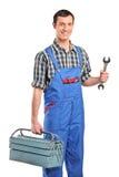 Un reparador en el verall que sostiene una caja de herramientas imagenes de archivo