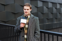 Un reporter maschio alla moda vestito dei giovani TV sta riferendo sulla via nella città fotografia stock