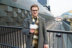 Un reportero feliz lleva un informe sobre la cámara en la calle imágenes de archivo libres de regalías