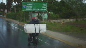 Un residente local monta una bicicleta con una caja grande en la lluvia almacen de video