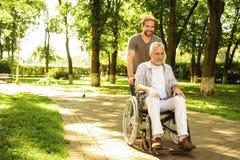 Un retraité sur un fauteuil roulant et son fils adulte marchent autour du parc Ils sont heureux et ont l'amusement Photographie stock
