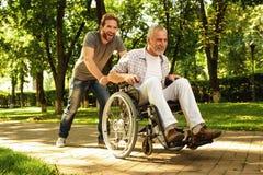 Un retraité sur un fauteuil roulant et son fils adulte marchent autour du parc Ils sont heureux et ont l'amusement Photos libres de droits