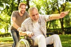 Un retraité sur un fauteuil roulant et son fils adulte marchent autour du parc Ils sont heureux et ont l'amusement Photo stock