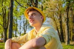 Un retrato de un adolescente feliz afuera, llevando una camisa y un sombrero amarillos contra un cielo azul, árbol verde Imágenes de archivo libres de regalías
