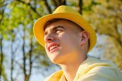 Un retrato de un adolescente feliz afuera, llevando una camisa y un sombrero amarillos contra un cielo azul, árbol verde Foto de archivo libre de regalías