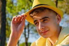 Un retrato de un adolescente feliz afuera, llevando una camisa y un sombrero amarillos contra el cielo azul y el árbol verde, man Fotografía de archivo libre de regalías
